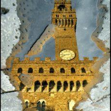 Firenze, Palazzo Vecchio riflesso nell'acqua sul selciato di Piazza della Signoria.